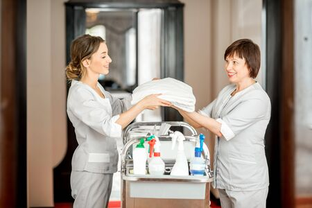 Senior chambermaid and young female assistant taking towels standing with maid cart full of cleaning stuff in the hotel corridor