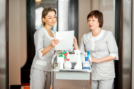 Senior chambermaid and young female assistant standing with maid cart full of cleaning stuff in the hotel corridor