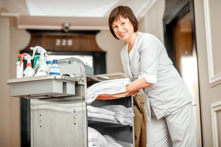 Älteres Frauenkammermädchen, das voll saubere Tücher vom Mädchenwagen des Reinigungsmaterials im Hotelflur nimmt