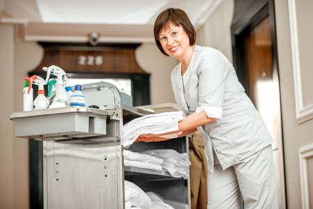 Senior woman chambermaid taking a clean towels from maid cart full of cleaning stuff in the hotel corridor