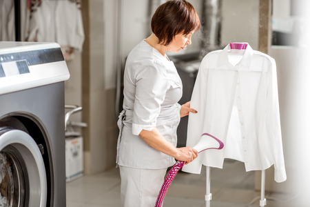 Senior washwoman in uniform ironing up a white shirt with vapor machine in the professional laundry 版權商用圖片