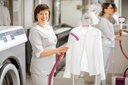 Portrait of a senior washwoman in uniform ironing up a white shirt with vapor machine in the professional laundry