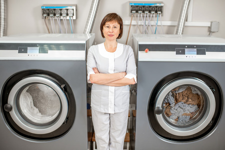 Portrait of a senior washwoman in uniform standing near the washing machines in the hotel laundry 스톡 콘텐츠