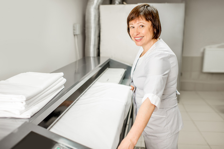 Senior woman in unifrom working with professional ironing machine in the laundry