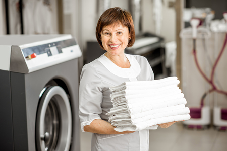 Portrait of a senior washwoman in uniform standing with towels in the hotel laundry