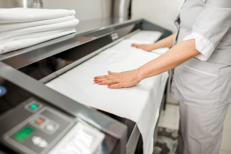 Ironing bedclothes with professional ironing machine in the laundry Archivio Fotografico
