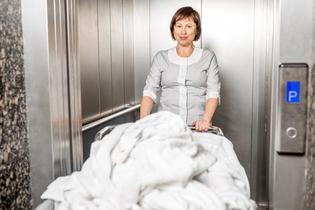 Senior Maid mit Kleidung Korb aus dem Aufzug im Hotel Standard-Bild - 95037817