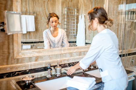 Young chambermaid in uniform cleaning a bathroom in the hotel