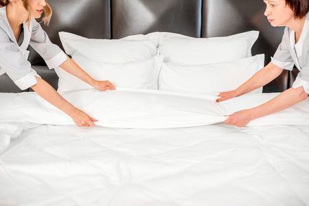 Two chambermaids in uniform making a bed with clean bedclothes in the luxury hotel bedroom