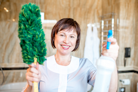 Portrait of a senior chambermaid standing with dust brush and cleanser in the hotel bathroom Stock Photo