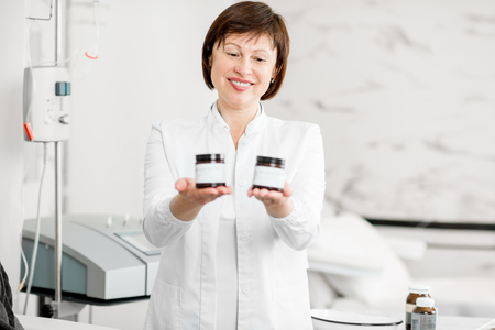 Smiling senior doctor holding a bottles with bio additives with white sticker to copy paste Stock Photo