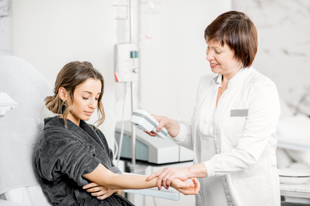 Senior doctor finding veins with vein scanner device to a young patient in a medical resort Stock Photo