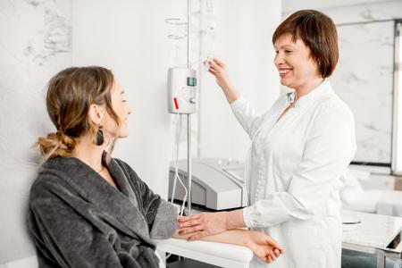 医療リゾートの血液ドロッパーによる血液浄化手順中にバスローブの若い患者を持つ上級医師
