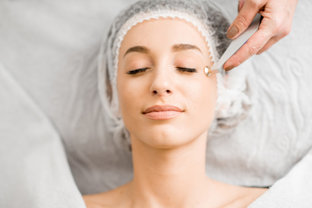 Young woman during the facial treatment procedure in the cosmetology office Stock Photo