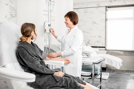 Doctor mayor con un paciente joven en bata de afeitar durante la operación de sangre con el peluquero de sangre en el complejo médico Foto de archivo - 95118293