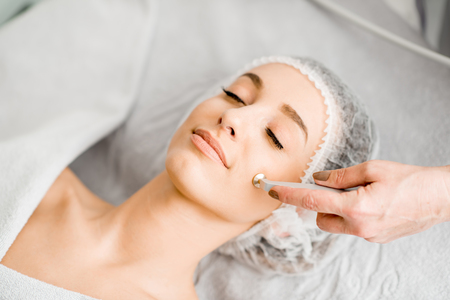 Young woman during the facial treatment procedure in the cosmetology office Foto de archivo