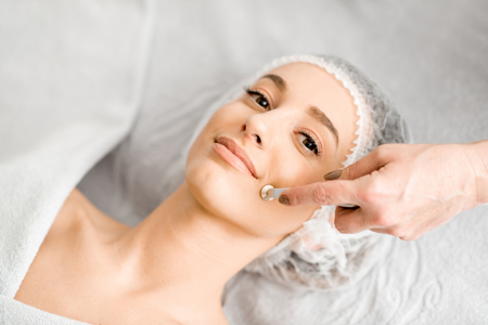 Young woman during the facial treatment procedure in the cosmetology office Stock Photo - 95118298