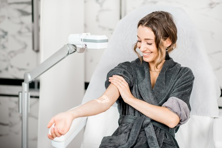 Young woman finding veins with vein scanner device for injection in medical resort Archivio Fotografico