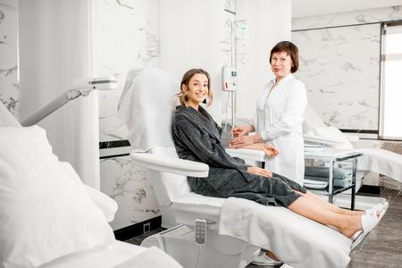 Doctor mayor con un paciente joven en bata de afeitar durante la operación de sangre con el peluquero de sangre en el complejo médico Foto de archivo - 95118339