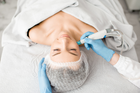 Young woman during the facial treatment procedure in the cosmetology office 写真素材
