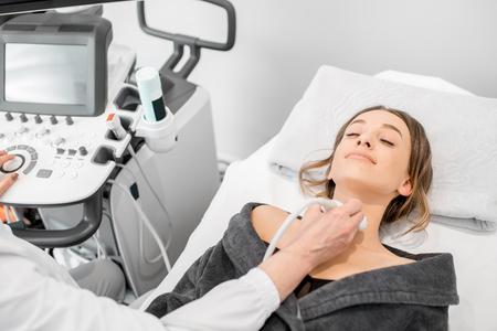 Paciente joven durante el examen de ultrasonido de una tiroides tumbada en el sofá en consultorio médico Foto de archivo