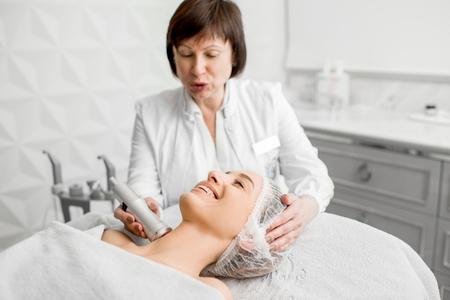 Senior vrouw schoonheidsspecialist gezicht procedure maken aan een jonge cliënt in een luxe medisch resort kantoor Stockfoto
