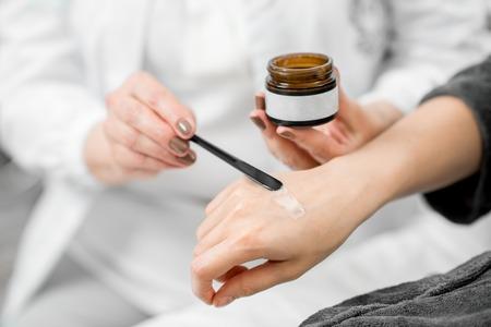 Doktor , der Creme auf den Arm des jungen Kunden anwendet , um zu versuchen