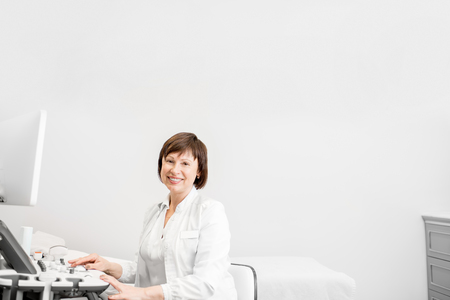 Portrait of a senior woman doctor in uniform with ultrasound equipment in the office