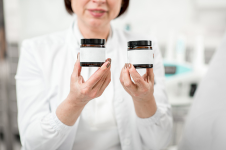 Doctor in uniform holding medicine bottles with white sticker to copy paste