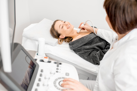 Senior doctor making an ultrasound examination to a young woman patient