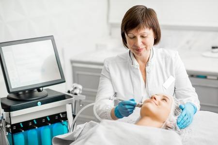 Femme âgée cosmétologue faisant procédure de visage à un jeune client dans un bureau médical de luxe Banque d'images - 95313020