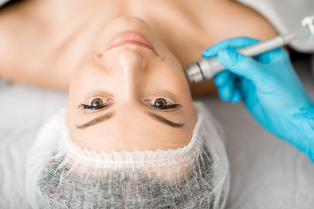 Young woman during the facial treatment procedure in the cosmetology office Stok Fotoğraf