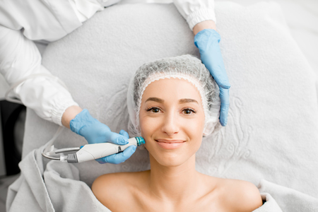 Young woman during the facial treatment procedure in the cosmetology office Banco de Imagens