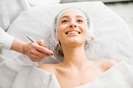 Young woman during the professional hydration procedure on the neckline in the cosmetological office Stockfoto - 95623821