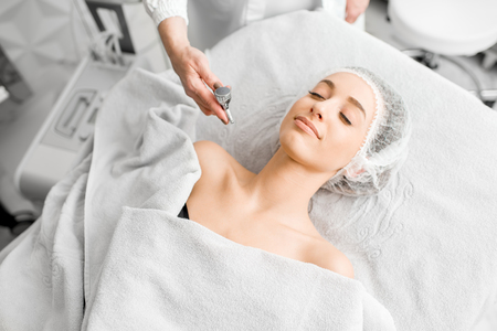 Young woman during the professional hydration procedure on the neckline in the cosmetological office
