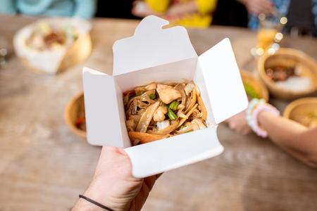 アジア料理の箱を屋内に持ち、食べ物がいっぱいのテーブルを背景に 写真素材 - 95651516
