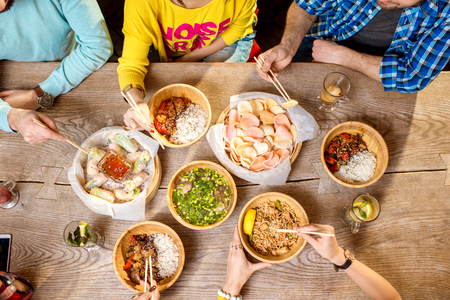 Top view on the table full of different asian meals served in the wooden plates and young people eating with sticks