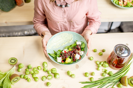 Holding a salad with beet and cheese on the wooden table with green ingredients and tea pot Stockfoto