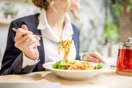 Geschäftsfrau , die Mittagessen mit Teigwaren und Früchtetee am veganen Restaurant auf dem grünen Hintergrund isst