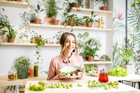 Portrait of a young woman holding a plate of salad sitting indoors surrounded with green flowers and healthy vegan food Stock Photo