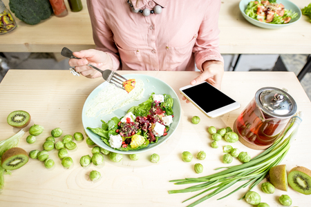 Woman eating salad and using smartphone at the table dwcorated with green food ingredients. Top view