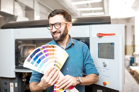 Funny portrait of typographer standing with color swatches at the printing manufacturing