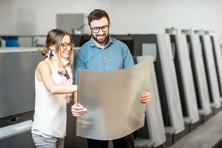 Young woman designer and print operator working together with offset plate standing at the print manufacturing Foto de archivo
