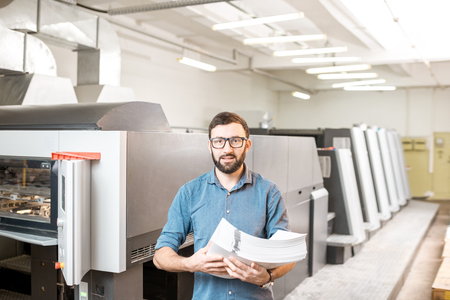 Portrait of a handsome typographer standing with stack of paper at the printing manufacturing with offset machine on the background