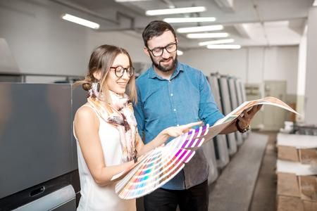 Jeune femme designer et opérateur d'impression travaillant avec des échantillons de couleurs debout à la fabrication d'impression Banque d'images - 95925647