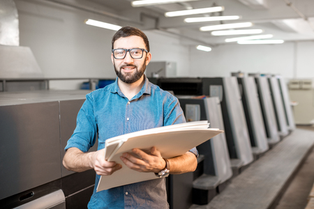 Portrait of a handsome typographer standing with stack of paper at the printing manufacturing with offset machine on the backgorund Stock Photo