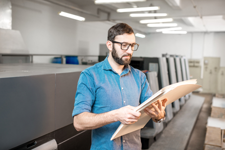 Portrait of a handsome typographer standing with stack of paper at the printing manufacturing with offset machine on the backgorund Reklamní fotografie
