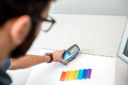 Measuring color on the paper print with spectrometer tool at the operating desk of the printing plant