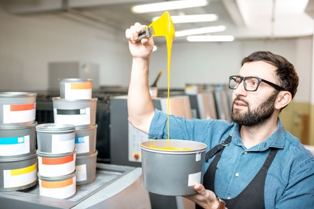 Typographer stiring yellow paint for offset machine standing at the printing manufacturing Stock fotó