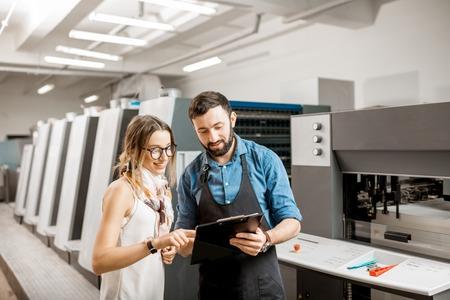 Joven diseñadora y operadora de impresión trabajando juntos en la fabricación de impresión con máquina offset en el fondo